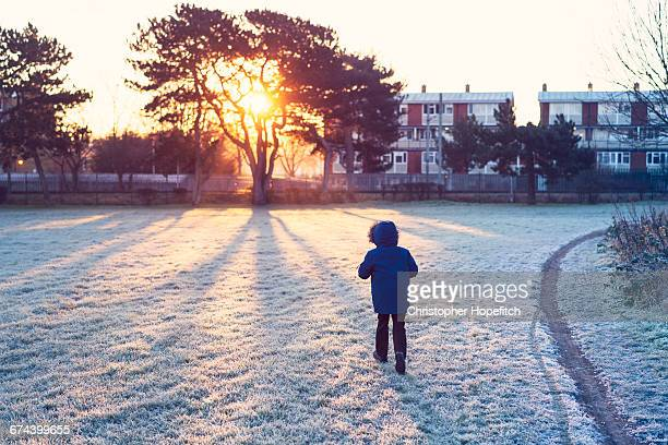 young boy walking to school - parka coat stock photos and pictures