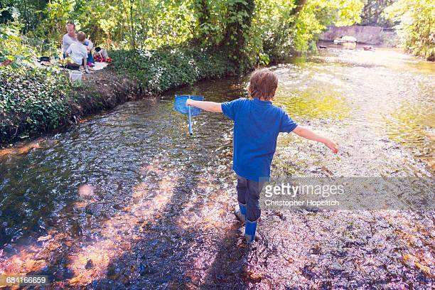 Young boy walking up a shallow river