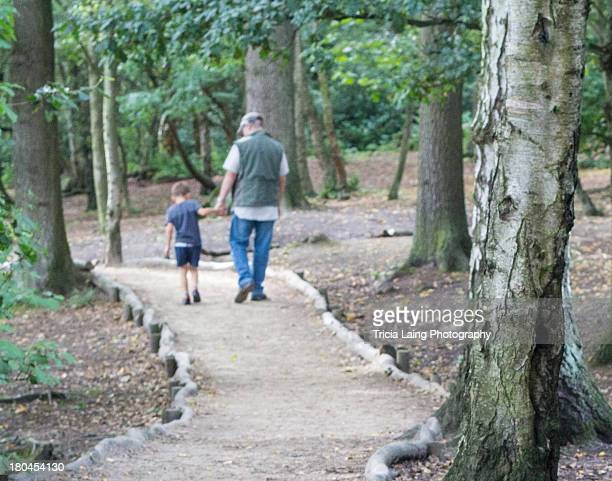 Young boy walking with and talking to his grandfat