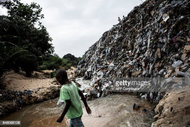 Young boy walks across a dirty river which bank is littered with garbage, on September 12, 2017 in the Ngaliema neighborhood in Kinshasa. / AFP PHOTO...