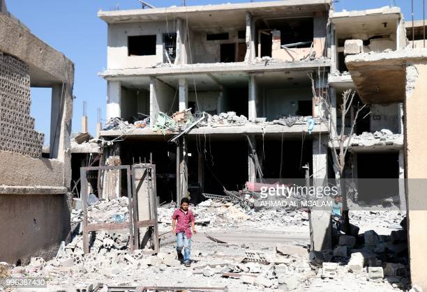 TOPSHOT A young boy walks among buildings destroyed during airstrikes by Syrian regime forces in the rebelheld town of Nawa about 30 kilometres north...
