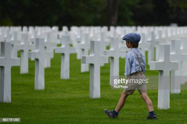 Young boy walks between the graves of fallen soldiers at the Normandy American Cemetery that contains the remains of 9,387 American military dead,...