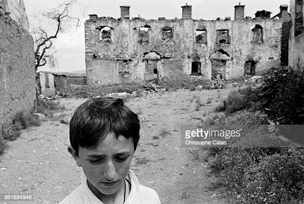 A young boy walks by the ruins of destroyed houses located in the area of Prizren destroyed during the war in Kosovo