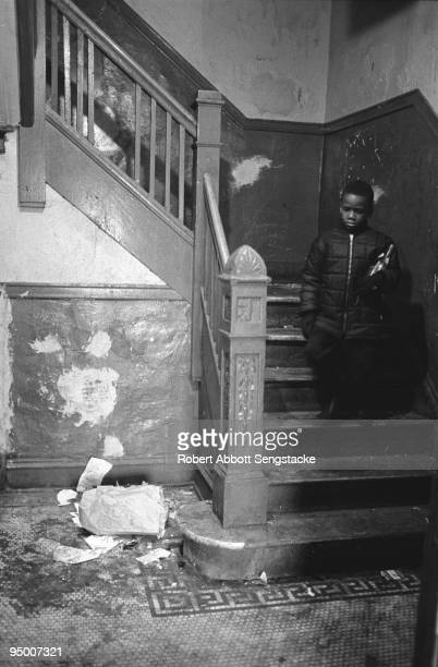 A young boy walks down the stairs of an apartment building in the Englewood neighborhood of Chicago 1967 Building conditions show neglect with debris...