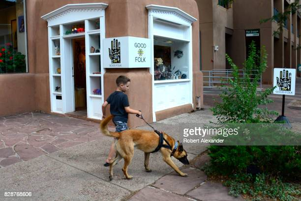 A young boy walks his dog along a sidewalk in Santa Fe New Mexico