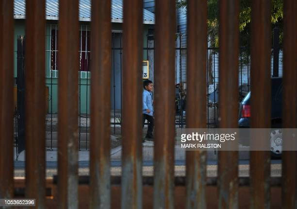 Young boy walks on the Mexican side behind a section of the new 30-foot high border wall at the US-Mexico border in Calexico, California, on October...