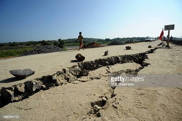 A young boy walks past cracks in the ground at Sintgu township Mandalay division in central Myanmar on November 12 2012 Myanmar rescuers struggled...