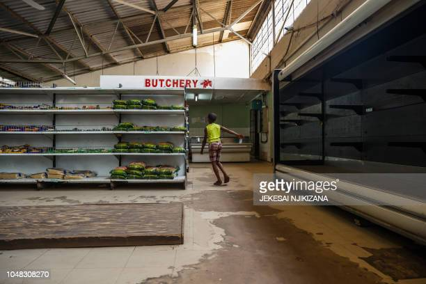 A young boy walks past empty shelves including those for bread and meat products in a groceries store in Harare as Zimbabwe is experiencing renewed...