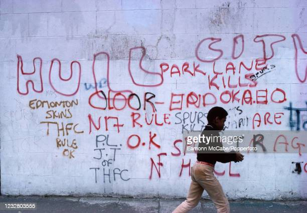 Young boy walks past football graffiti to which the National Front insignia has been added in London, England, circa 1980.