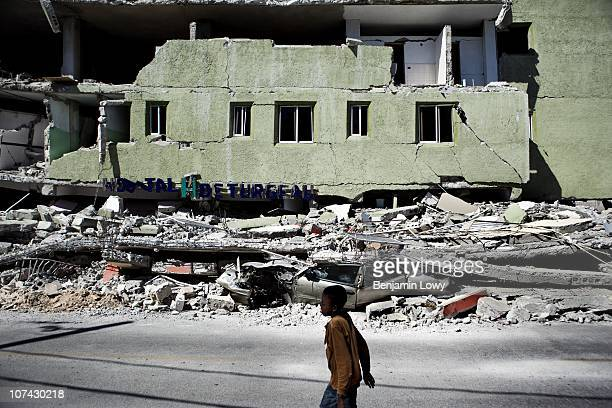 Young boy walks past the remains of a pancaked hospital in Port au Prince, Haiti. On January 12, 2010 Haiti was struck by a magnitude 7 earthquake...