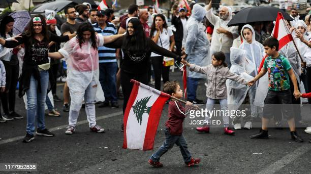 A young boy walks with a Lebanese flag past protesters some wearing ponchos gathering during a demonstration on the eighth day of protest against tax...
