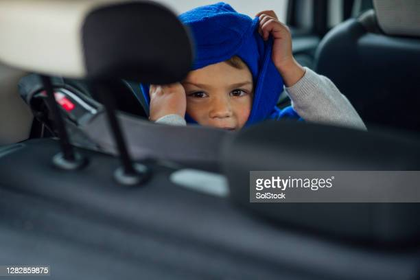 young boy warming up in the car - warm clothing stock pictures, royalty-free photos & images