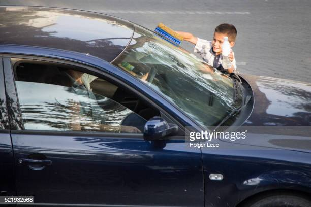 Young boy washes windscreen of car