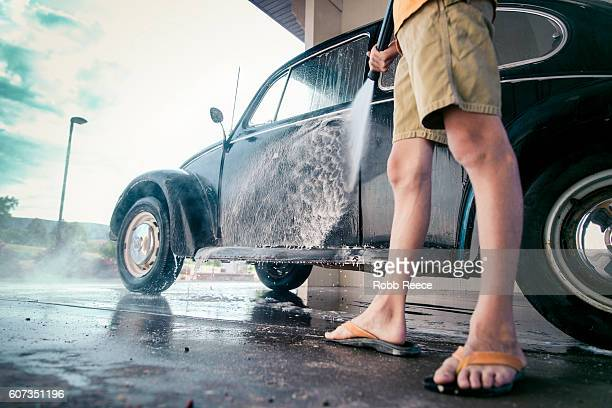 A young boy washing a 1967 vintage Volkswagen Bug at a carwash