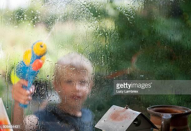 Young boy washing the windows with water gun