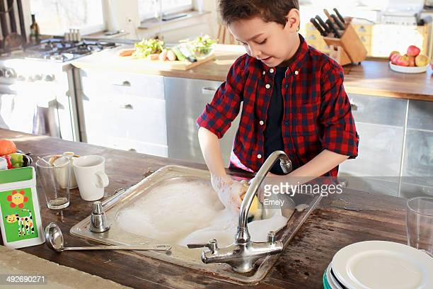Young boy washing up in kitchen