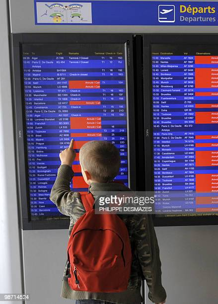 A young boy watches an electronic board announcing the cancelled flights in red on April 20 2010 at the Saint Exupery airport in Lyon eastern France...