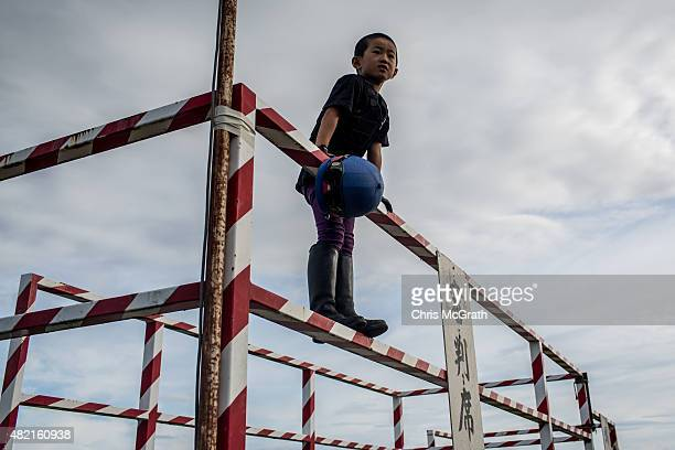 A young boy watches on as his father trains for the Kacchukeiba ahead of the Soma Nomaoi festival at Hibarigahara field on July 24 2015 in Minamisoma...