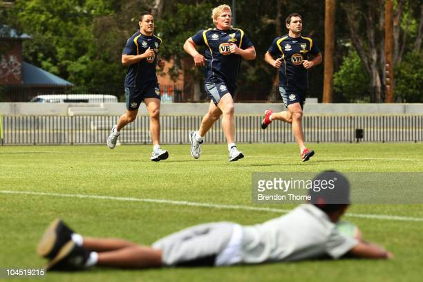 A young boy watches on as Jarryd Hayne Ben Hannant and Cameron Smith during an Australian Kangaroos training session at Redfern Oval on September 29...