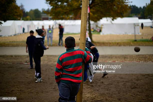 A young boy watches refugees from Afghanistan and Syria play volleyball on an improvised field at a refugee camp on October 20 2015 in Celle Germany...