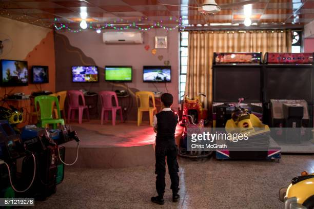 A young boy watches video games at the Mosul Amusement Park on November 4 2017 in Mosul Iraq The theme park was shut down under ISIS occupation and...