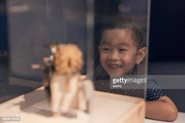 young boy watching crafts indoors - museum stock photos and pictures
