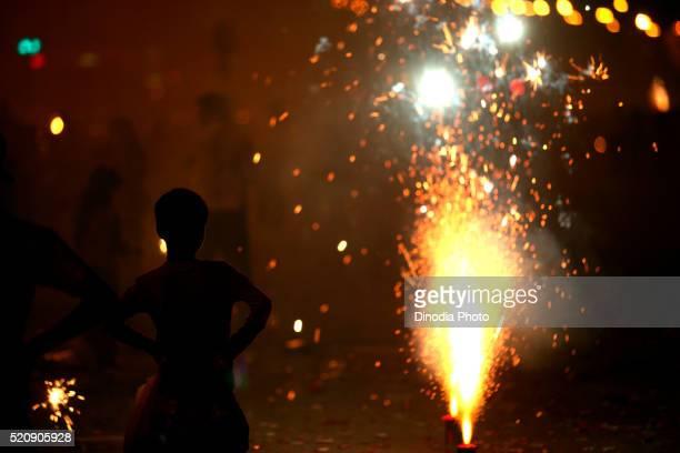 Young boy watching fire crackers bursting in Marine Lines in Bombay Mumbai, Maharashtra, India