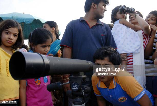 Young boy watching flamingoes through a telescope Bombay Natural History Society organised a Flamingo Festival
