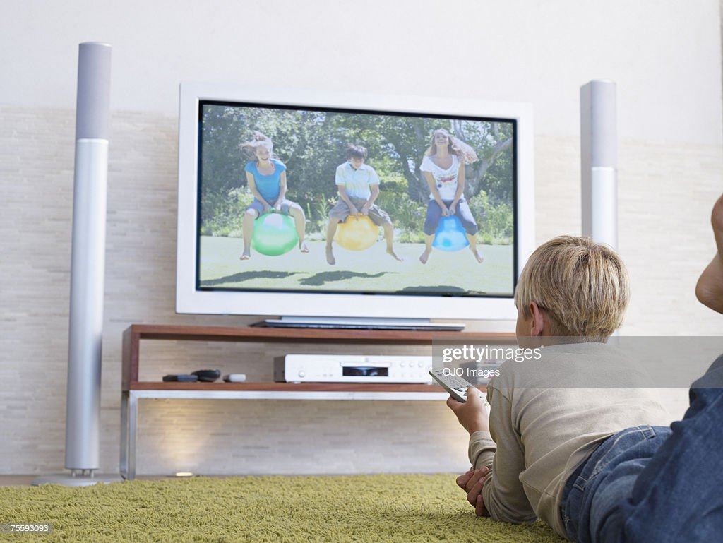 A young boy watching television : Stock Photo