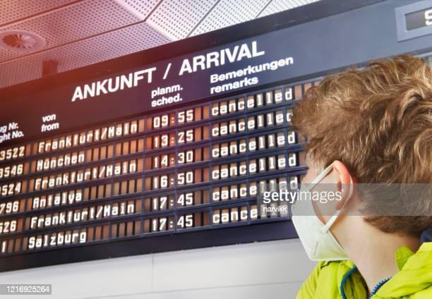 すべてのフライトがキャンセルされたボードを見ている若い男の子 - 取り消し ストックフォトと画像