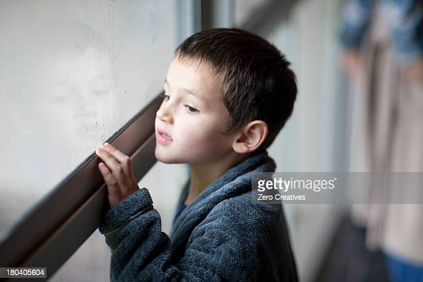 Young boy watching through porch window