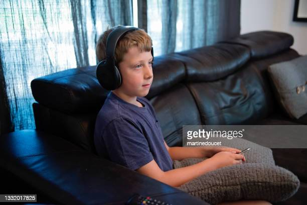 """young boy watching tv in living room. - """"martine doucet"""" or martinedoucet stock pictures, royalty-free photos & images"""