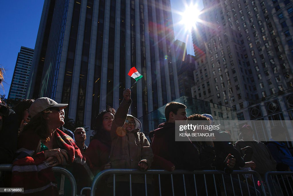 A young boy waves a little Italian flag during the annual Columbus Day parade in New York on October 10, 2016. Columbus Day is a national holiday in many countries in the Americas and elsewhere which officially celebrates the anniversary of Christopher Columbus' arrival in the Americas on October 12, 1492. / AFP / KENA