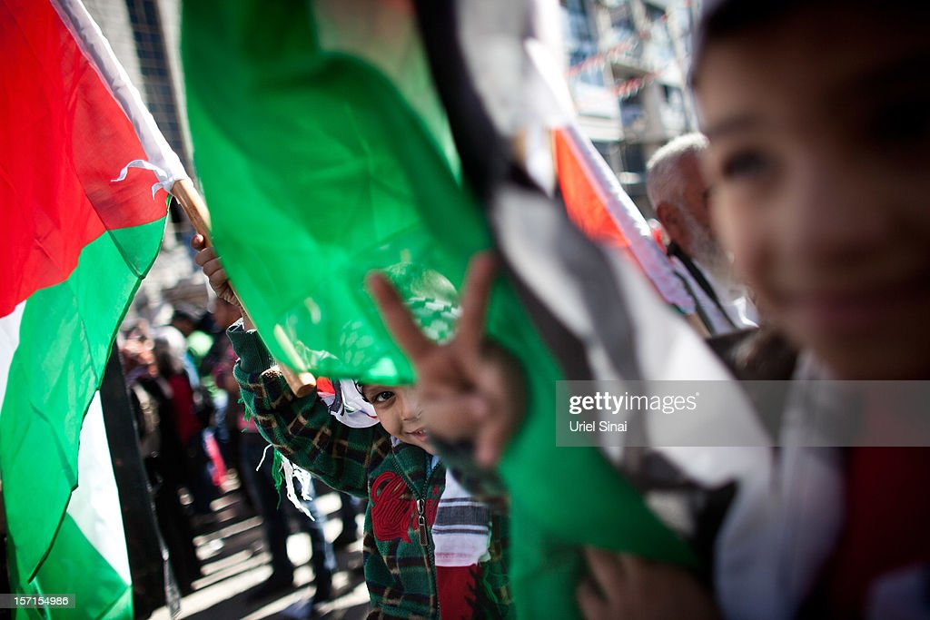A young boy waves a Palestinian flag and makes a peace sign during a rally on November 29, 2012 in Ramallah, West Bank. Palestinian leader Mahmoud Abbas will speak to The UN General Assembly later today in a bid for Palestinians to achieve 'non-member state' status, a move that is widely expected to be passed despite opposition from Israel and the United States.