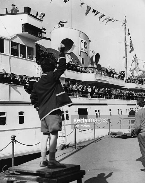 A young boy waving to passengers aboard the pleasure steamer the 'Royal Sovereign' as it leaves on its first trip of the season from Tower Pier...