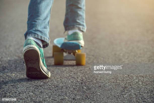 young boy wear jeans and green shoes is skateboarding on the street. - patinar fotografías e imágenes de stock