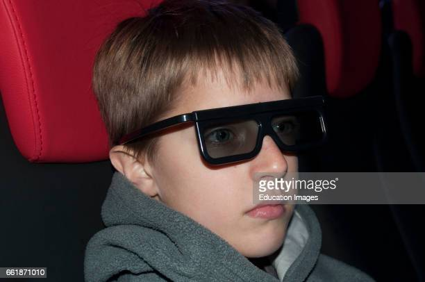 Young boy wearing 3D glasses watching a 3D movie at the cinema