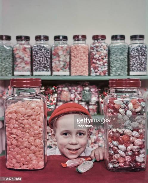 Young boy wearing a cap poses with jars of boiled sweets from a sweet shop in England in April 1949. Children all over the country are celebrating...