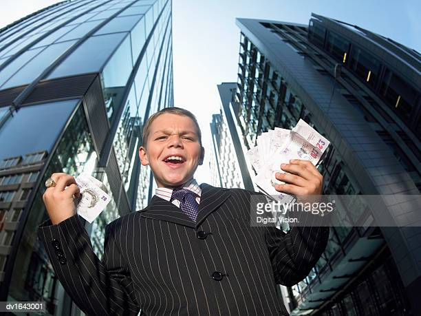 Young Boy Wearing a Full Suit Stands in Front of Skyscrapers Shouting and Holding Wads of Banknotes