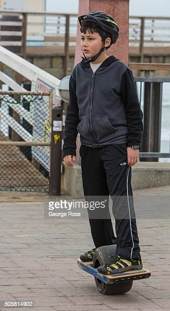 A young boy wearing a helmet rides an unusual onewheel allterrain 'hoverboard' on January 17 2016 in Pismo Beach California Because of its close...