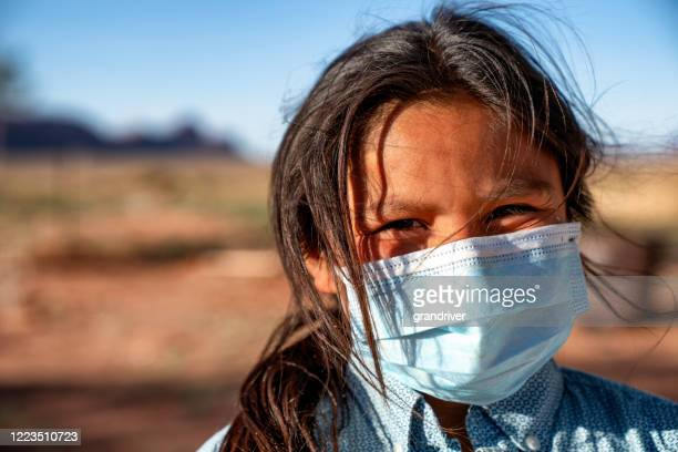 a young boy wearing a mask over his mouth and nose because of the coronavirus pandemic on the navajo reservation in arizona - indigenous north american culture stock pictures, royalty-free photos & images