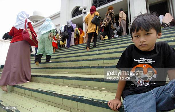 A young boy wearing a Tshirt supporting presidential candidate Amien Rais waits for his mother as she joins other Muslim women for prayer at a mosque...