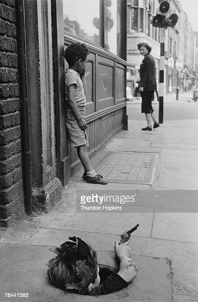 A young boy wearing an Indian headdress hides in a coal hole and takes aim with a toy pistol London 7th August 1954 Original publication Picture Post...