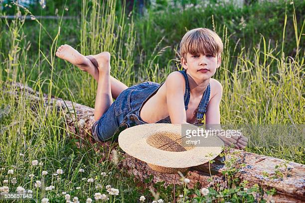Young boy wearing blue overalls laying on fallen tree