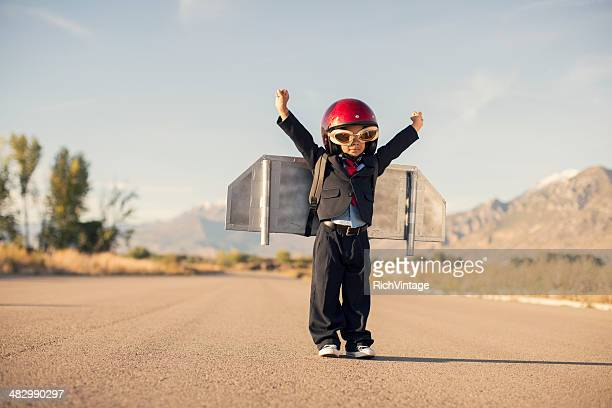 Young Boy Wearing Business Suit and Jet Pack Flies