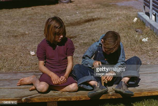 A young boy wearing denim overalls builds a model airplane as a young girl seated next to him watches in a Farm Security Administration labor camp in...