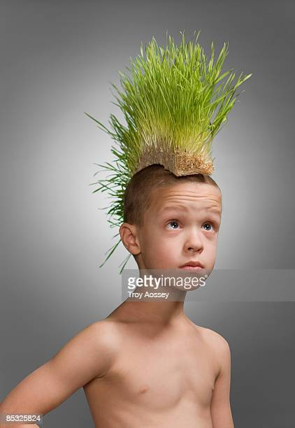 young boy wearing faux grass mohawk on head