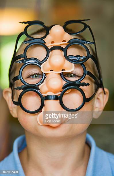 Young boy wearing four pairs of novelty glasses