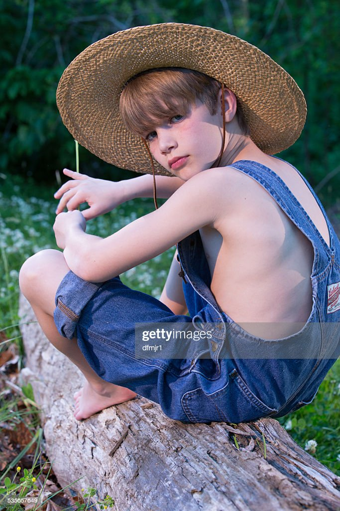 Young Boy Wearing Overalls Sitting On Tree Wearing Straw