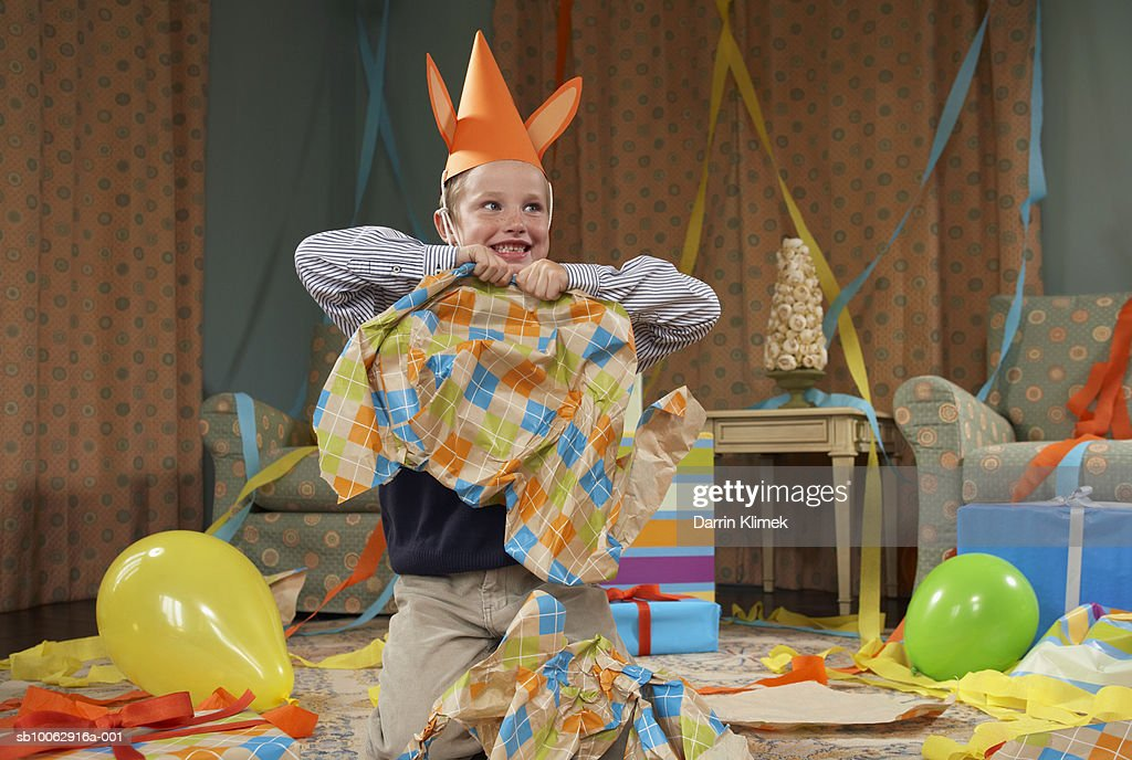 Young boy (6-7) wearing party hat, making mess in room after party : Stock Photo